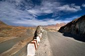Road Going Across Himalaya Mountains Along Indus River Under Blue Cloudy Sky. India, Ladakh