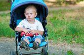 Little boy in a pram on a walk
