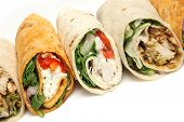 Variety of wrap sandwiches with chicken and feta cheese.