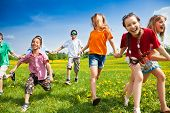 foto of dandelion  - Large group of children running in the dandelion spring field - JPG