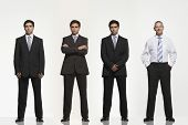 Full length portrait of businessmen standing side by side against white background