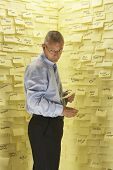 Businessman standing in front of wall covered in sticky notes