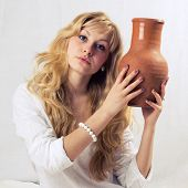 stock photo of loamy  - Portrait of a young blonde girl with jug in the white background - JPG