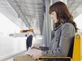 Side view of a businesswoman reading a book at train station bench