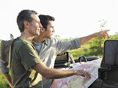Side view of two male friends with map on bonnet of jeep