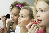 stock photo of slumber party  - Closeup side view of three girls side by side putting on makeup and lipgloss - JPG