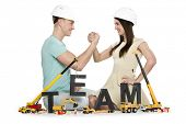Team building concept: Smiling young man and woman building the word team along with construction ma