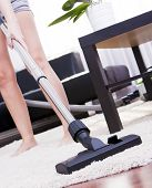 Young Attractive Woman Is Cleaning Vacuum On Carpet.