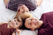 Happy Father, Little Daughter And Mother Lie On White Double Bed And Look Up. Focus On Woman.