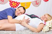 Happy Pregnant Wife And Husband Lie On Carpet And Man Listens Belly.