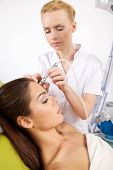 Portrait of attractive beautiful young adult brunette woman having a stimulating facial treatment fr