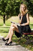 beautiful blonde girl writing a book in green garden