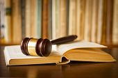 picture of courtroom  - Open law book with a judges gavel resting on top of the pages in a courtroom or law enforcement office - JPG