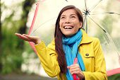 Autumn woman happy after rain walking with umbrella. Female model looking up at clearing sky joyful