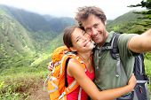Hiking couple - Active young couple in love. Couple taking self-portrait picture on hike. Man and woman hiker trekking on Waihee ridge trail, Maui, USA. Happy romantic interracial couple.