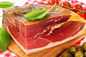 detail of whole prosciutto block with vegetable on a wooden cutting board