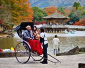 NARA, JAPAN - NOVEMBER 18: A rickshaw runner enthusiastically explains the ride to tourists November