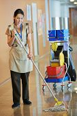 Adult cleaner maid woman with mop and uniform cleaning corridor pass or hall floor of business build