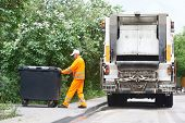 stock photo of recycle bin  - Worker of municipal recycling garbage collector truck loading waste and trash bin - JPG