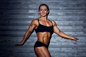 Woman bodybuilder on wall background.