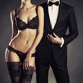 stock photo of erotic  - Art photo of a young couple in sensual lingerie and a tuxedo - JPG