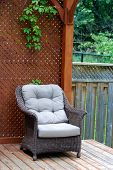 stock photo of screen-porch  - Wicker outdoor chair on a wooden deck - JPG