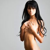 Beautiful woman covers her naked breasts with her hand