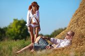 Erotic scene between brooding man lying on hayloft and his lovely girl