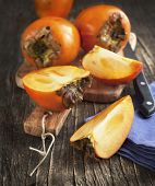 Fresh Ripe Persimmons On A Wooden Table