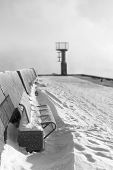 pic of boggy  - Blue metal bench on snowy mole and small beacon or lighthouse at the end of the pier - JPG