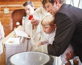 Little Baby Boy Being Baptized In Catholic Church Holding By Father.