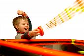 picture of won  - A child who has won his air hockey game with a red mallet in his hand - JPG