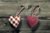 2 pieces of fabric hearts polka dots plaid on wood background