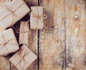 stock photo of gift wrapped  - Several gift boxes postal parcels wrapped in brown kraft paper tied with a rope on a wooden board - JPG