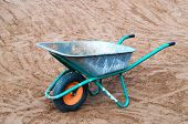 foto of wheelbarrow  - Empty wheelbarrow in the sand - JPG