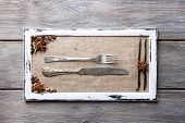 Wooden frame, spices and vintage cutlery  on color wooden background