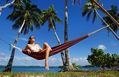 Young Woman In Bikini Sitting In A Hammock Between Palm Trees, Ofu Island, Vavau Group, Tonga