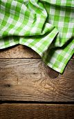 Wooden background with green checkered kitchen towel