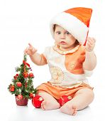 Beautiful baby in santa hat near christmas tree