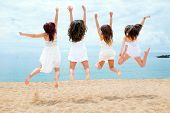 Teen Girls Jumping On Beach