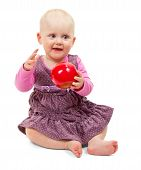 Sweet little girl sits with an apple in his hand
