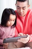 Asian Girl And Dad Using Tablet