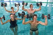 Happy fitness class doing aqua aerobics with foam dumbbells in swimming pool at the leisure centre