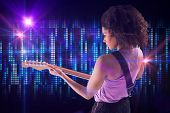 Pretty girl playing guitar against digitally generated cool pixel background