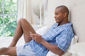 Happy man sitting on bed and texting on phone at home in the bedroom
