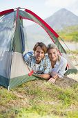 Attractive couple smiling at camera from inside their tent on a sunny day