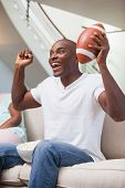 Bored woman sitting next to her boyfriend watching sport at home in the living room