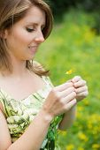Close-up side view of cute young woman holding flower in field