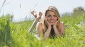 Pretty blonde in sundress lying on grass smiling at camera on a sunny day in the countryside