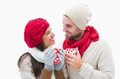 Attractive young couple in warm clothes holding mugs on white background